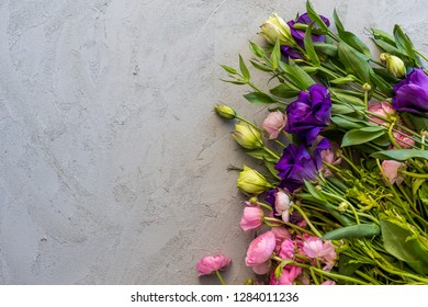Floral flatlay. Upper view shot of pink ranunculus and purple lisianthus over concrete tabletop., Copy space.