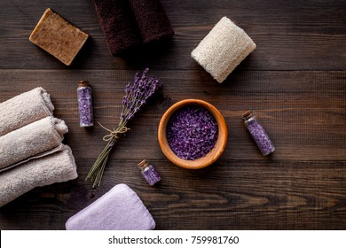 Floral foot spa with lavender. Spa salt, sponge, soap, towel on dark wooden background top view copyspace