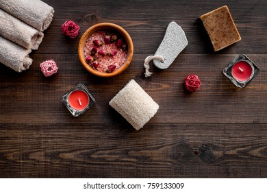 Floral foot spa with rose. Candles, salt, pumice stone, soap, buds on dark wooden background top view copyspace