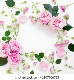 Floral frame composition with roses flowers, leaves and buds on white background. Flat lay, top view. Frame background