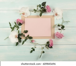 Floral frame consists of pink roses and white orchid flowers and empty paper with place for text on wooden background. Top view. Flat design. Copy space.