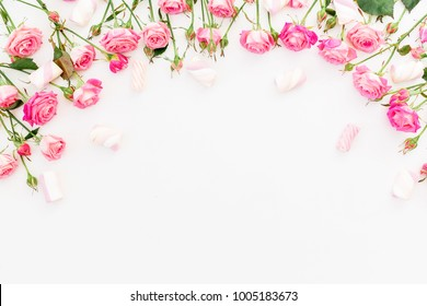 Floral frame made of pink roses and marshmallow on white. Flat lay, Top view.