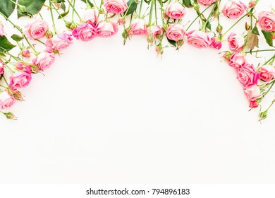Floral frame made of pink roses on white background. Flat lay, Top view.