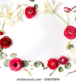 Floral frame of pink and red roses or ranunculus, white tulips and green leaves on white background. Flat lay, top view