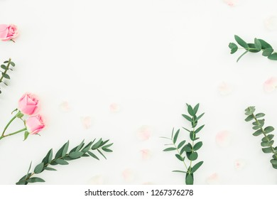 Floral frame of pink roses and eucalyptus branches on white background. Flat lay, top view