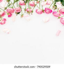 Floral frame of pink roses and marshmallow on white background. Flat lay, Top view.