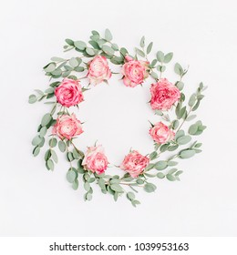Floral frame wreath of red rose flowers and eucalyptus branches on white background. Flat lay, top view floral mockup with empty space.