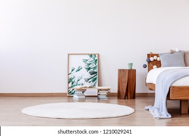 Floral graphic in frame next to wooden bedside table and bed with pillows and blankets, white round carpet on the floor, copy space on the wall