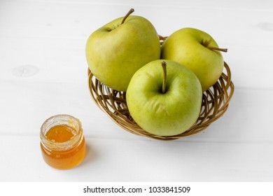 Floral honey and a basket of green apples on a textile tablecloth. Glass saucer and wooden spoon, kitchen utilities. Home made organic mask ingredients. Healthy eco lifestyle. Food blog illustrations.
