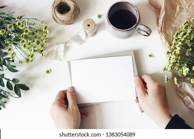 Floral lifestyle composition. Mockup scene with mums flowers, greenery and cup of coffee on white table. Female hands holding blank greeting card. Floristry business concept. Flat lay, top view.