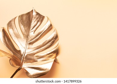 Floral minimal style concept. Exotic summer trend. Golden tropical palm monstera leaf on nude color background. Shiny and sparkle design, fashion concept.