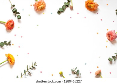 Floral minimalistic frame with fresh flowers and little hearts on the white paper background. Top view. Copy space