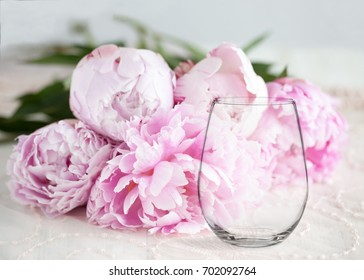 Floral mock-up of a stemless wine glass, in front of a bunch of peonies, perfect for businesses who sell decals, vinyl stickers, just overlay your design