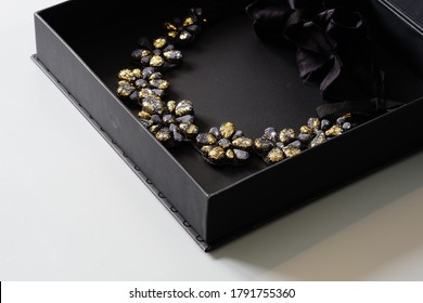 floral necklace, woman jewelry in black box on a gray background, goth, dark fashion. black and gold necklace,