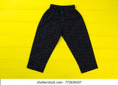 Floral pants on yellow wooden table. Loose fitting and comfy loungewear item. Bright clothing background for special offer.