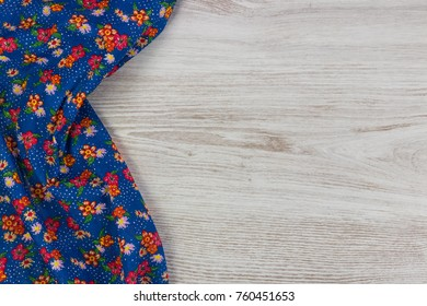 Floral pattern cloth napkin on empty wooden background. Top view with space for your text.