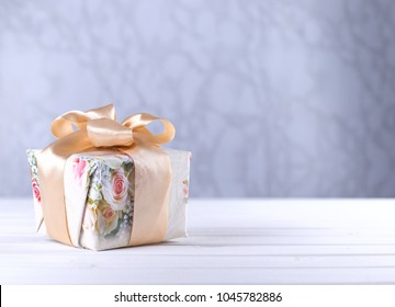 Floral pattern gift box tied with ribbon on wooden table with copy space mother`s day