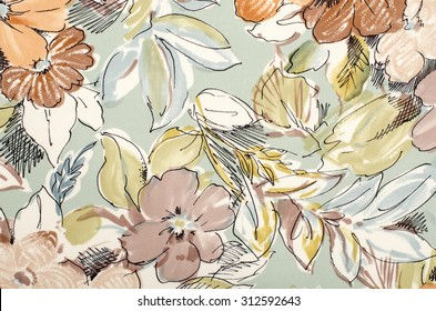 Floral pattern on fabric. Brown flowers with blue and green leaves print as background.