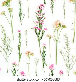 Floral pattern with pink and beige wildflowers, green leaves, branches on white background. Flat lay, top view. Valentine's background