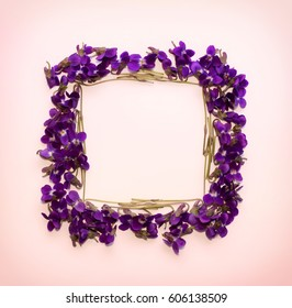 Floral pattern square Frame made of small forest flowers violet with empty space for text on a  on pink background. Flat lay, top view. mock up for text, phrases, congratulations, lettering