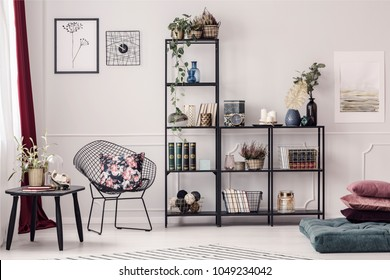 Floral pillow placed on a metal chair standing next to a black rack with decorations and books in bright cozy living room interior