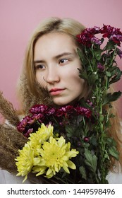 Floral portrait of young adult female with blond hair on pink background