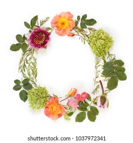 Floral round crown (wreath) with flowers and leaves. Flat lay, top view. Creative arrangement with roses, gray grefsheim leaves, sevenbark and waterlily.
