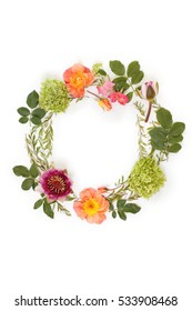 Floral round crown (wreath) with flowers and leaves. Flat lay, top view. Creative arrangement with pink and orange roses, gray grefsheim (spiraea cinerea) leaves, sevenbark (hydrangea) and waterlily.