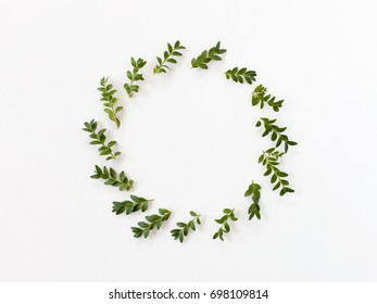 Floral round frame with branches and leaves on white background. Flat lay, top view