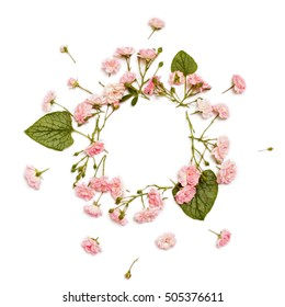 Floral round frame on white background. Flat lay, top view. Ornament with rose flowers and green brunnera leaves with space for text.
