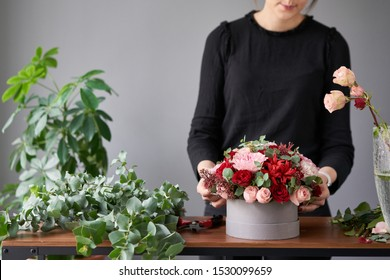 Floral shop concept . Florist woman creates flower arrangement in a round box. Beautiful bouquet of mixed flowers. Handsome fresh bunch. Flowers delivery