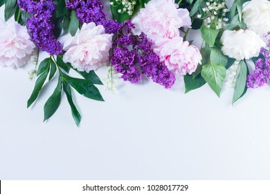 Floral spring border - lilac, peonies and lilly of the walley flowers on white background, flat lay scene with copy space