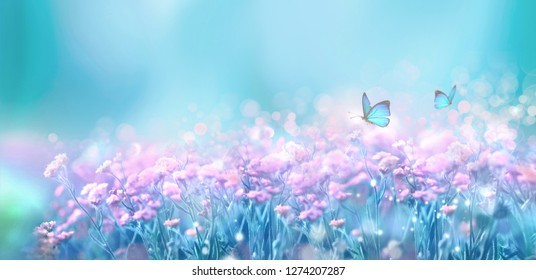 Floral spring natural landscape with wild pink lilac flowers on meadow and fluttering butterflies on blue sky background. Dreamy gentle air artistic image. Soft focus, author processing.
