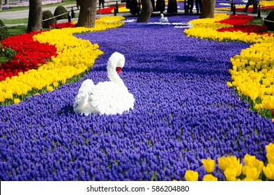 Floral swan among blue flowers and tulips