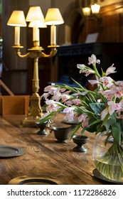 Floral table decoration on oak table. Luxury period dining room. Soft serene image of a formal luxuriant fine dining area with an historic feel. Suggestions of wealth, romance and history.