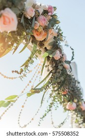 Floral wedding arch from roses on sky background
