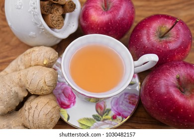 Floral and white cup and plate porcelain set with fruit tea made with red apples, ginger and cinnamon as ingredients on wooden background. Winter hot drink. Closeup top view.