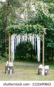 Floral wooden arch with macrame and candles at a rustic wedding ceremony