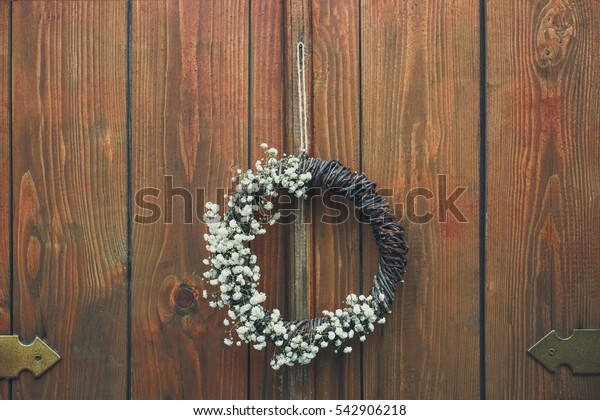Floral wreath with beautiful flowers hanging on wooden background