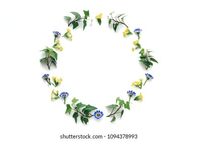 Floral wreath with colorful spring flowers and green leaves on white background.