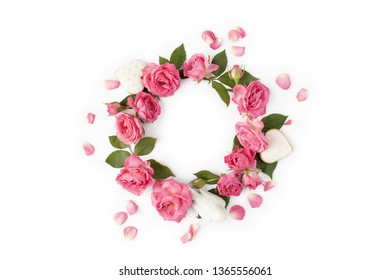 Floral wreath made of roses and leaves. Natural round frame isolated on white. Holiday concept. Top view.