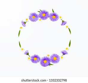 Floral wreath made of violet flowers and chamomile on white background. Flat lay. Top view with copy space.