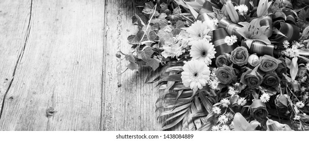 Floral wreath on weathered wooden background with copy space in stunning black and white