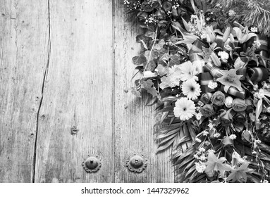 Floral wreath on weathered wooden door with copy space in stunning black and white