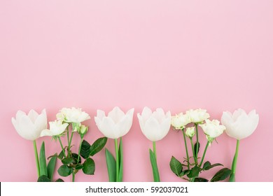 Floral's background. Floral bouquet made of white roses and tulips on pink background. Flat lay, top view. Woman day background.
