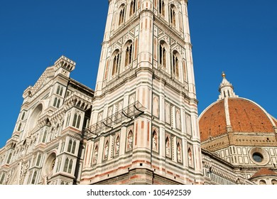 Florence Cathedral of Santa Maria del Fiore or Duomo di Firenze, detail of the facade, Brunelleschi's dome and Giotto's bell tower against the blue sky.