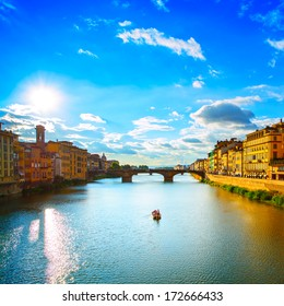 Florence or Firenze, Ponte Santa Trinita medieval Bridge landmark on Arno river and a boat, sunset landscape. Tuscany, Italy.