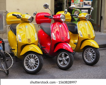 Florence, Italy - 07 21 2019: Vespa scooters standing on the street of Florence. Two yellow Vespa Sprint 150 Sport and red Vespa Primavera 150. Vespa is Italian scooter brand manufactured by Piaggio.