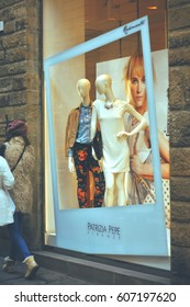 Florence, Italy –march 2, 2014,  two women go out looking at Patrizia Pepe window shop with dressed mannequins from new collection at the central street of Florence at evening