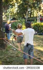 FLORENCE, ITALY - 20 JUNE 2015 - A father teaches his daughter the acrobatics art on a slackline on June 20, 2015 in Florence (Italy)